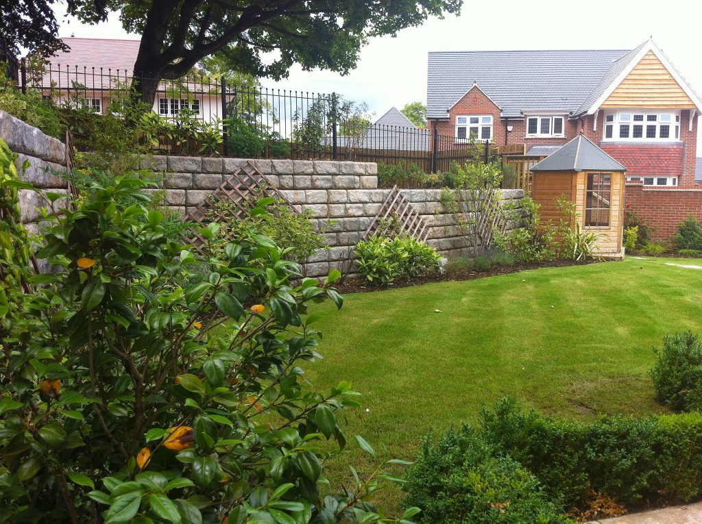 Garden with green grass and bushes surrounded by a stone fence.