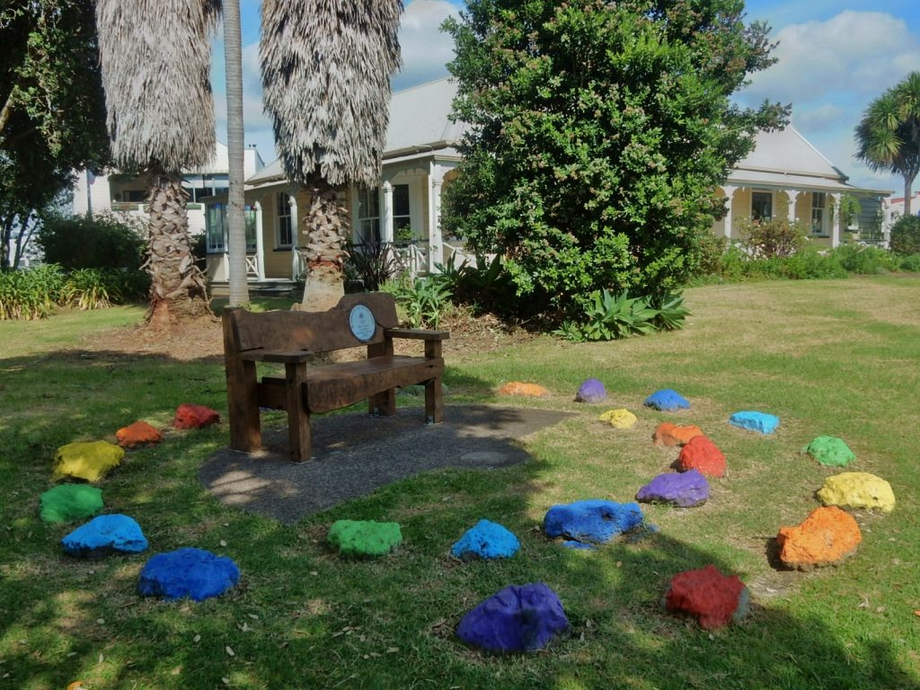 Rocks painted in orange, yellow, green, blue and purple in a garden and circling a bench.